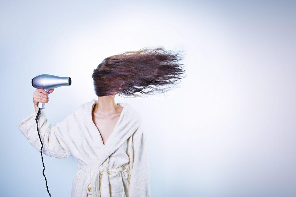 vrouw met bruin haar en een fohn puntjes afknippen