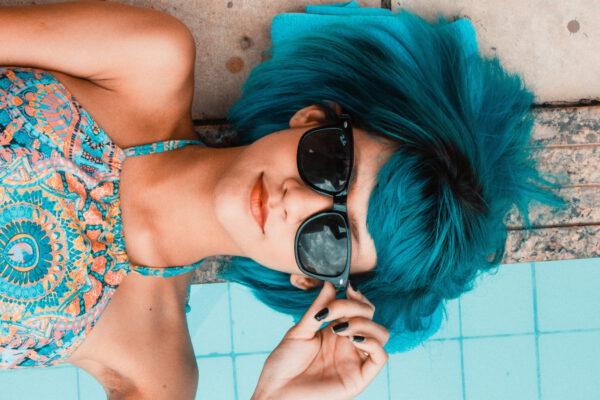meisje met groen haar aan het zwembad met zonnebril