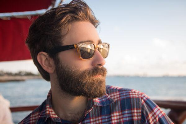 man met baard en zonnebril op zeilboot