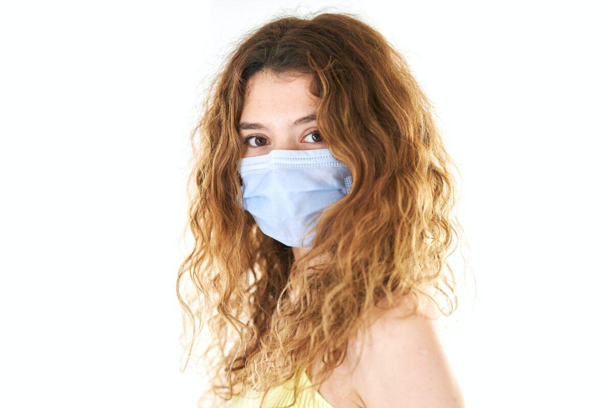 Blanke vrouw kijkt naar camera met mondmasker op