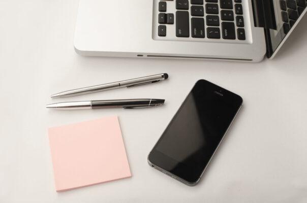laptop, pennen, notitieblokje en iPhone